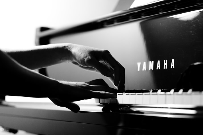 Photograph of two hands playing the piano.