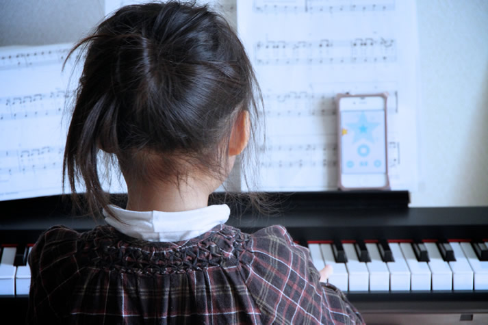 Young girl having a piano lesson on a digital piano.