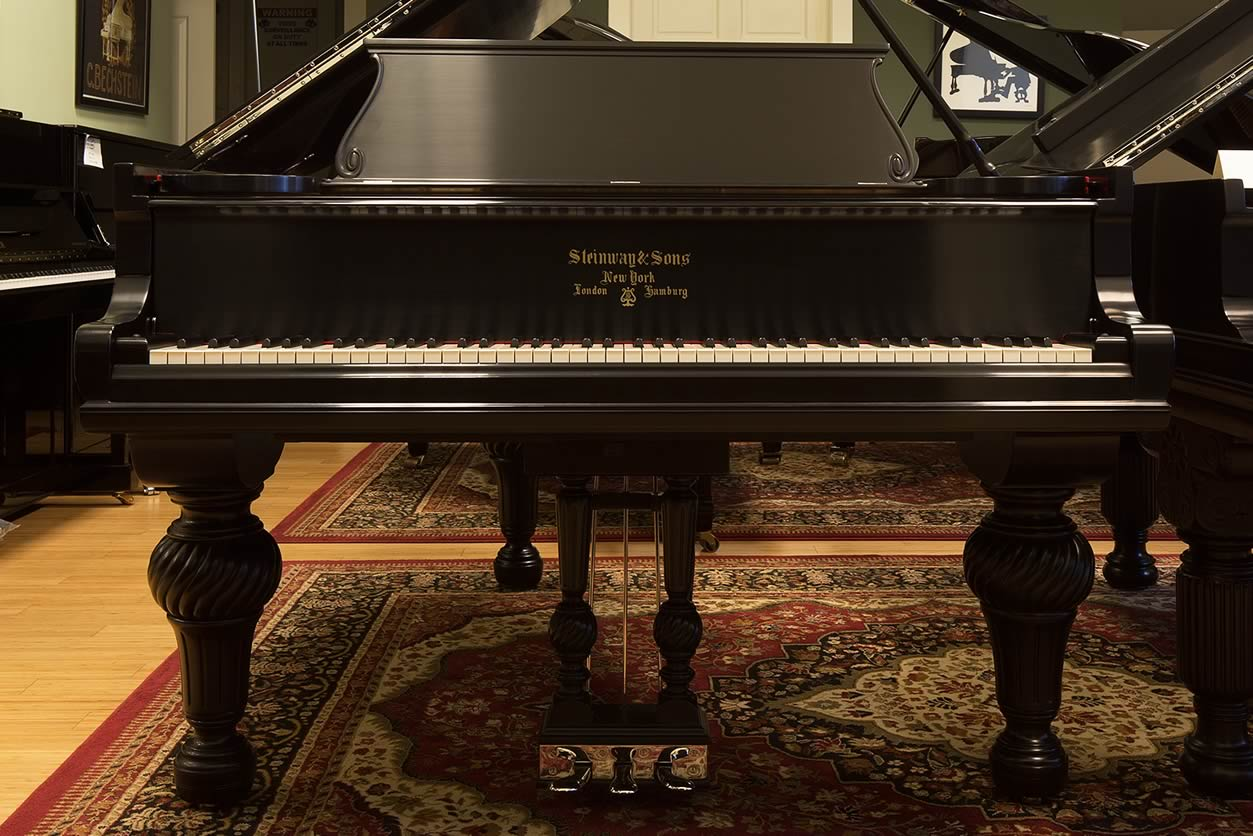 Main Gallery Image: Angled, close-up of the fallboard with logo on a Steinway & Sons ebony, Art Case O parlor grand piano.