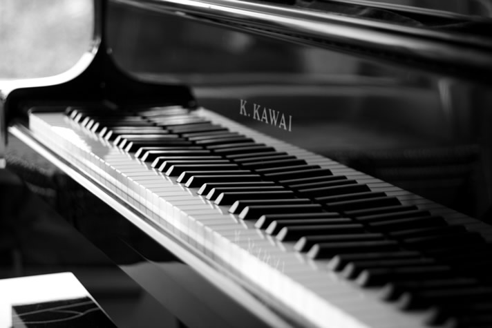 Angled view of the keyboard and fallboard with logo of a Kawai upright piano.