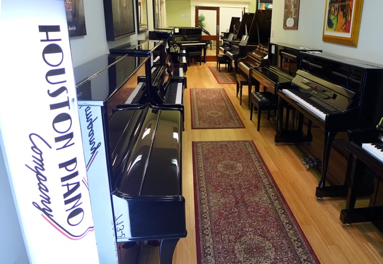 Hallway lined with upright and grand pianos, leading to Houston Piano Company's recital hall.