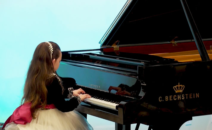 Girl performing on a C. Bechstein grand piano at HPC Grand Recital Hall.