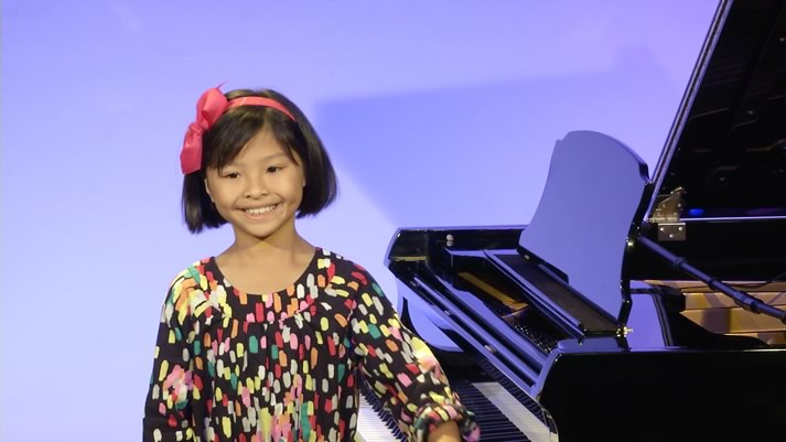 Girl enjoying applause from her piano performance at HPC Grand Recital Hall.