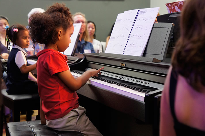Students performing on Roland digital pianos for their families at HPC Grand Recital Hall.
