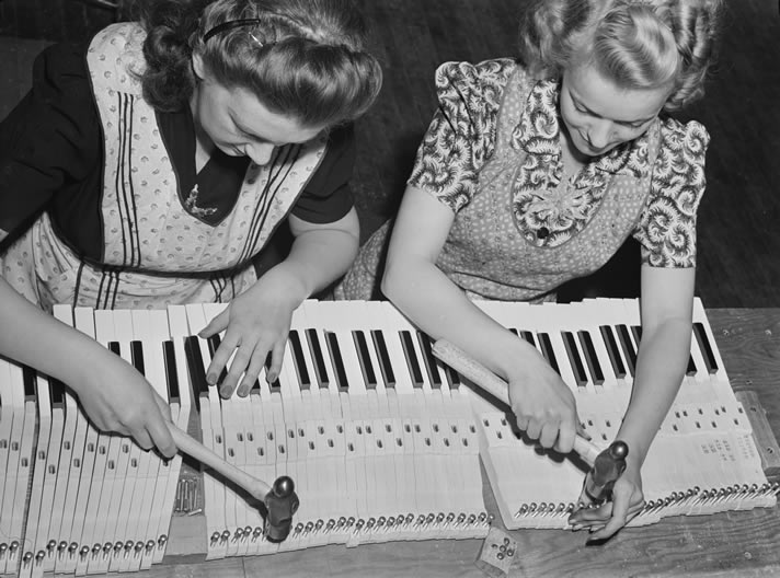 Two woman assembling parts of a piano keyboard.