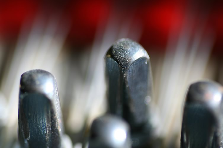 Macro close-up of piano tuning pins, photographed by Scott Robinson.