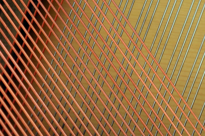 Close-up view of the crosshatch of piano strings.