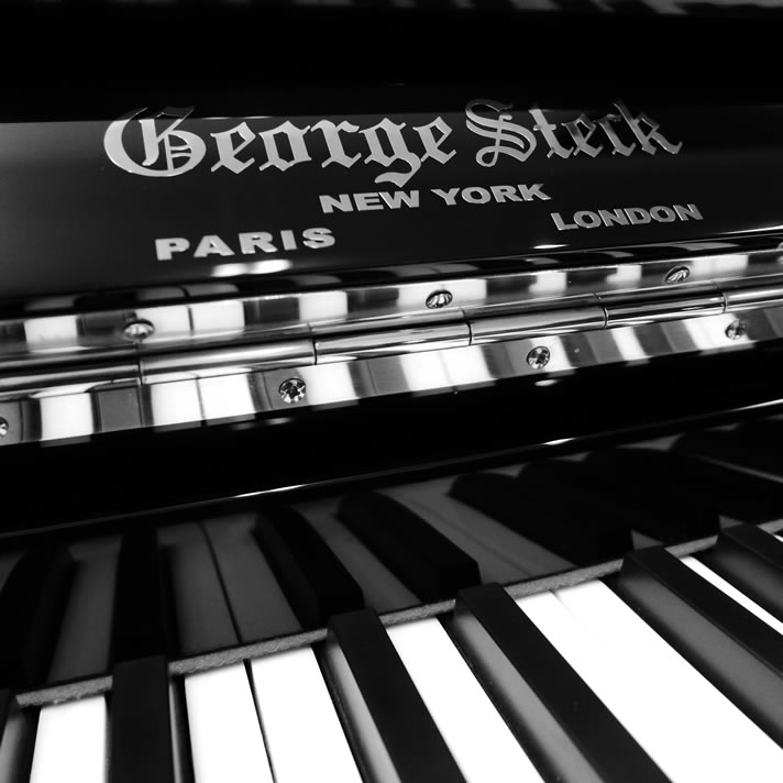 Close-up of a George Steck glossy black piano and its logo.