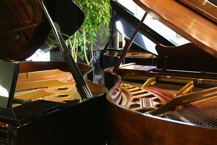 Three grand pianos converging with open lids.