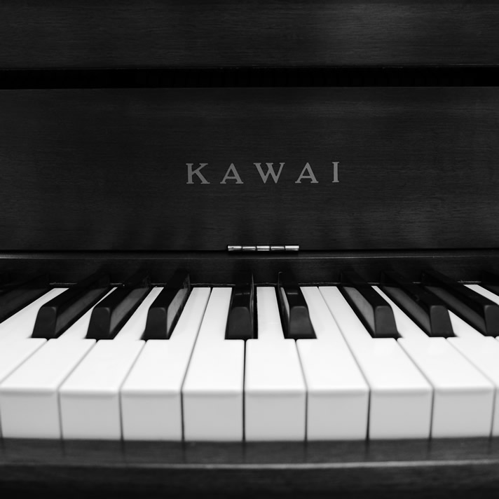 Close-up of Kawai grand piano keys and logo.