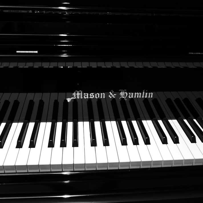Close-up of a Mason & Hamlin black, glossy grand piano keys and logo.