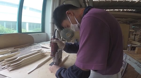 Employee from Pearl River hand-finishing spruce ribs for the soundboard of a piano.