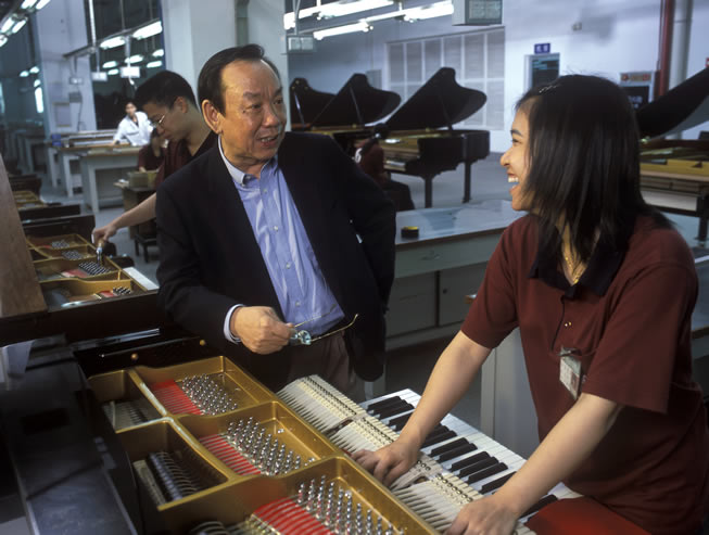 Zhicheng Tong, CEO, talking with a Pearl River piano factory employee.