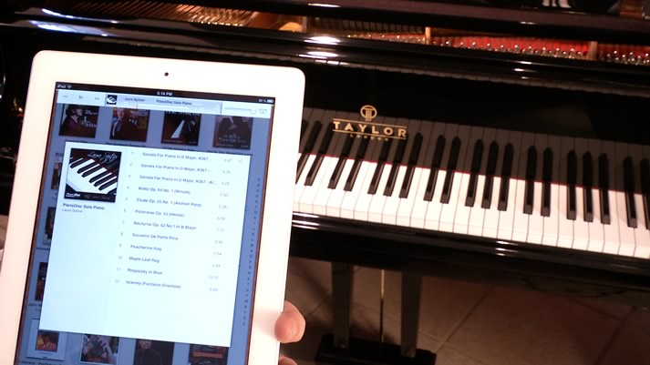 PianoDisc iQ iPad Air with a Taylor grand piano in the background.