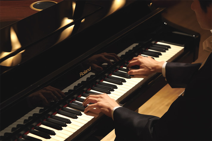 Pianist playing a Roland V-Piano grand digital piano.