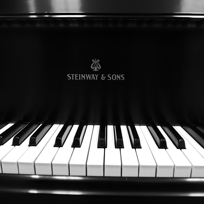 Close-up of the logo and keyboard for a Steinway & Sons piano.