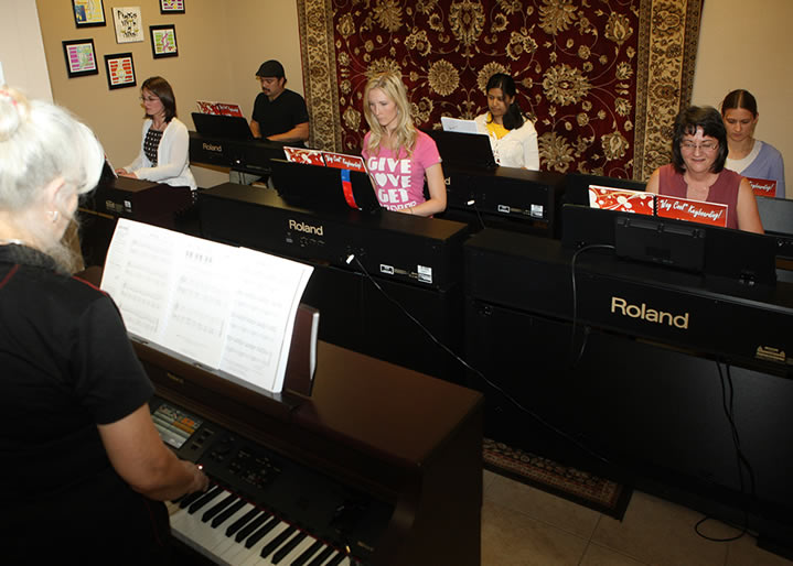 Adults taking group piano lessons on Roland digital pianos at HPC School of Music.