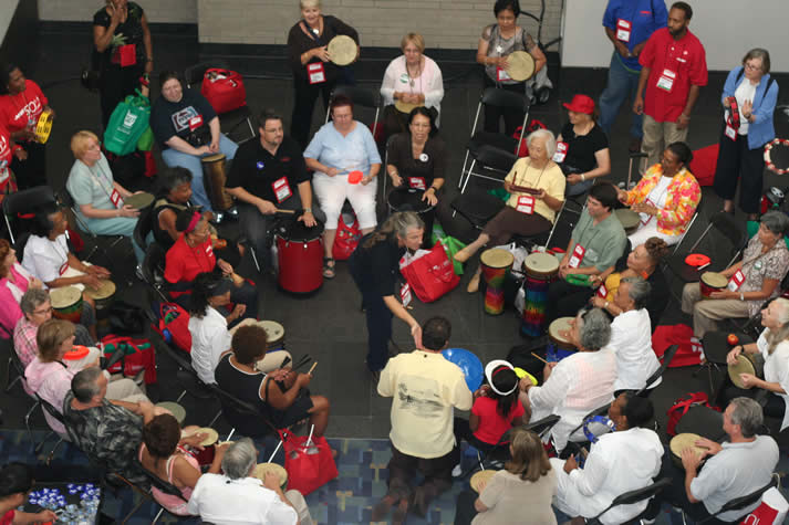 All types of people participating in a drum circle sponsored by AARP.